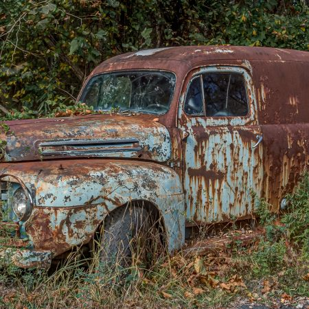 Classic 1940s Ford Utility truck van in weeds.