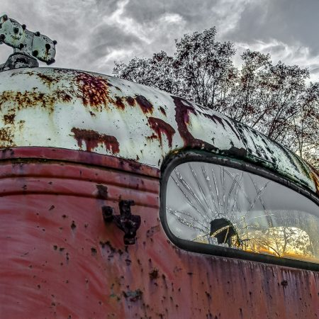 Sunset through the cracked rear window of a 1940s vintage truck.