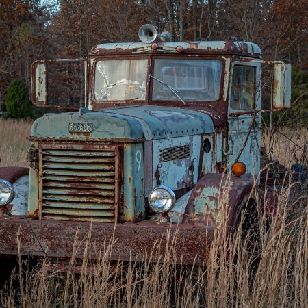 Rusted and peeling 1940s Peterbilt Truck with cracked window and in field of wheat
