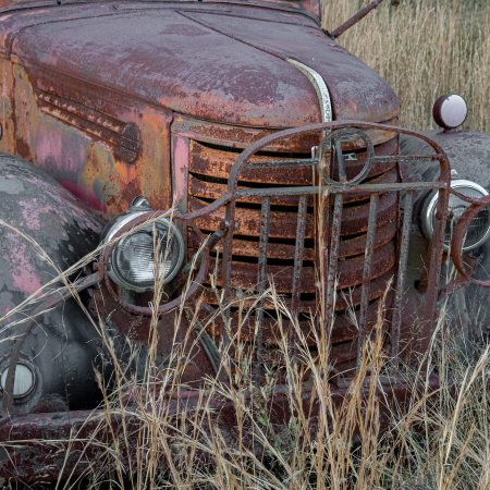 Rusted 1930s farm truck with metal grill and headlight protector.