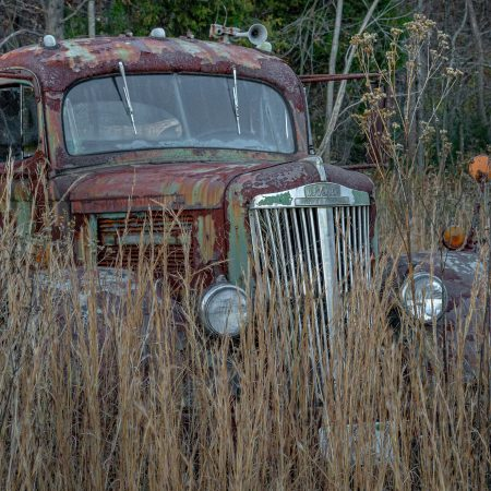 Rusted White Superpower 1930s truck in field of tall grass.