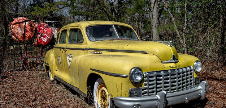 1940s Yellow Doge Cab with cab license identification and vintage Coke signs in rear.