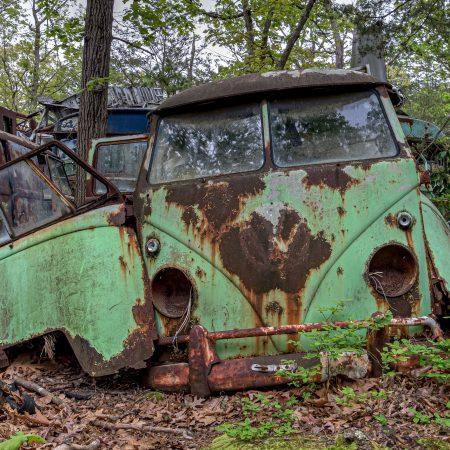 Vintage 1960s green Volkswagen VW counterculture bus with advanced rust.