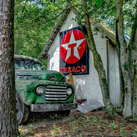 Vintage green Ford 1940s Truck next to classic Texaco sign.