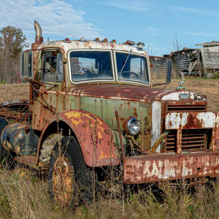 Vintage Semi Mack truck in a field with abandoned building in rear.