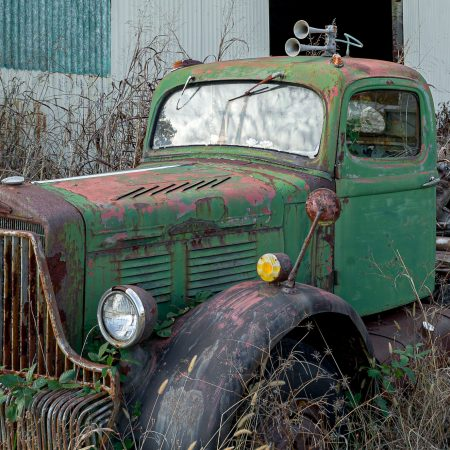Vintage 1940s farm trucks with rust and multi-colored paint finish.