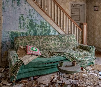 Abandoned house living room with sofa, peeling paint, crocheted pillow and upholstered couch.